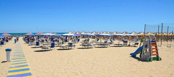 Лежаки, зонтики и детская горка на пляже в городе Монтесильвано, Италия