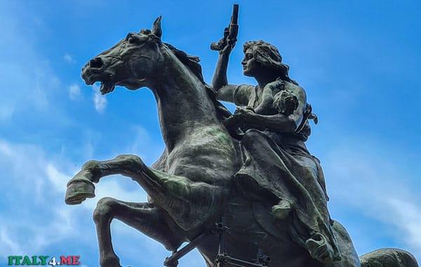 Анита Гарибальди с младенцем и пистолетом в руке скачет на лошади