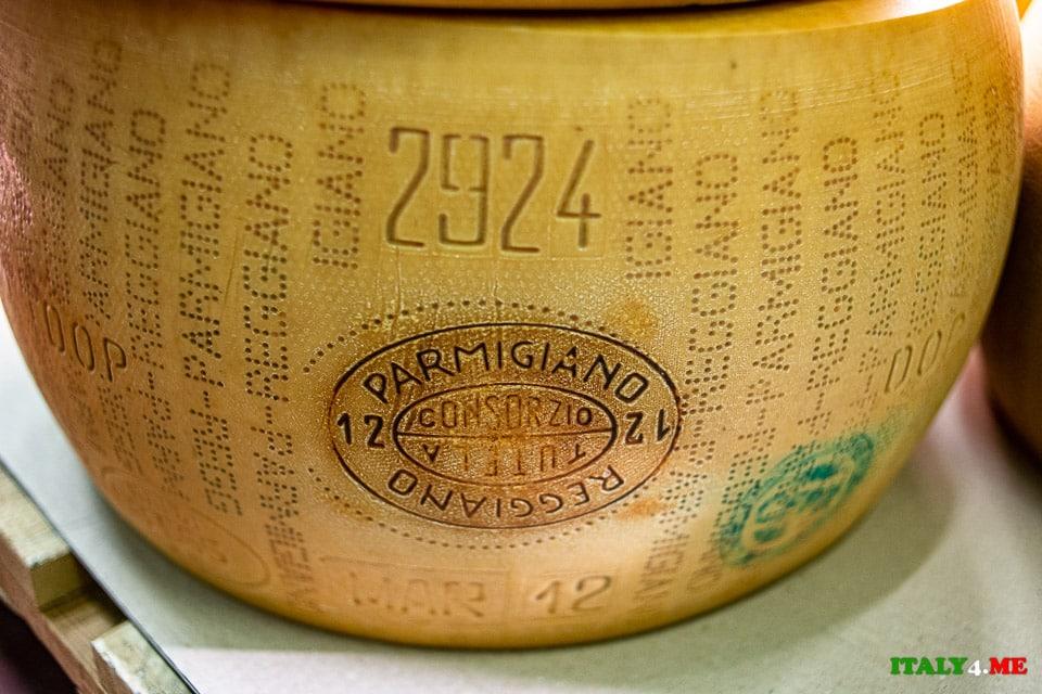 Головка сыра Пармезан с датой производства, знаком качества и названием