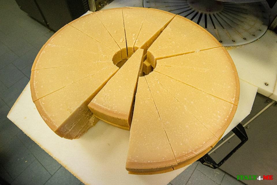 Нарезка головки Пармезана на треугольные куски для продажи